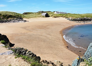 one of the many sandy beaches on llanddwyn island