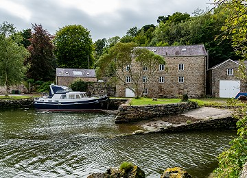 The old water mill and harbour at high tide at Pwllfanogl