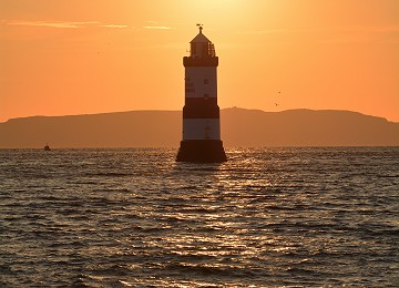 Trwyn Du lighthouse with sunrise above