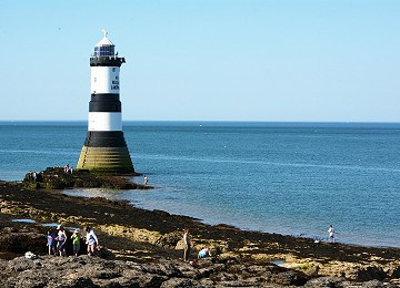 Trwyn Du lighthouse at Penmon with visitors on the shore