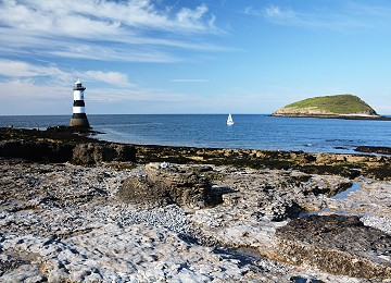 Trwyn du lighthouse with puffin island and yacht sailing